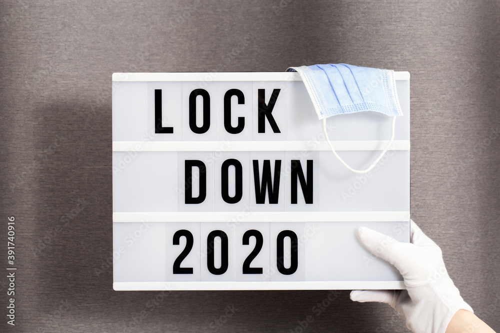 Fototapeta Hands in white gloves hold Light box with message lockdown 2020 and Surgical protective mask. Word of the Year 2020 is lockdown.