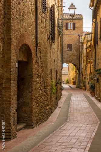 Fotomural The empty narrow winding back street of a historic hilltop town in Tuscany Italy