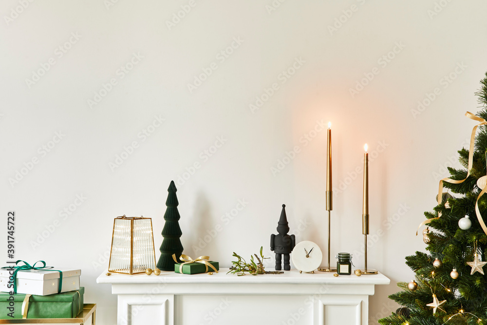 Fototapeta Christmas composition on the white chimney at the living room interior with beautiful decoration. Christmas tree and wreath, candles, stars, light. Copy space. Template.
