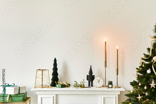 Christmas composition on the white chimney at the living room interior with beautiful decoration. Christmas tree and wreath, candles, stars, light. Copy space. Template.