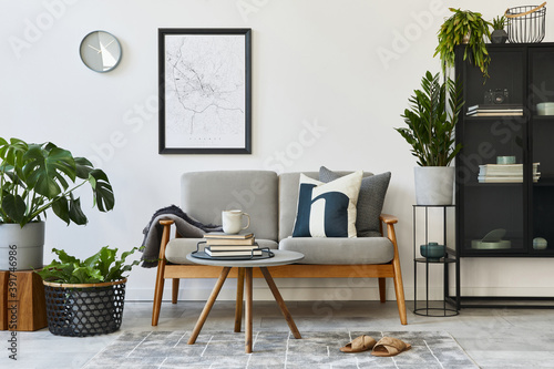 Modern retro concept of home interior with design grey sofa, coffee table, plants, furniture, mock up poster map, decoration and personal accessoreis. Stylish home decor of living room.