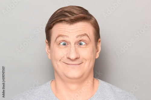 Платно Portrait of funny happy man making goofy face with crossed eyes