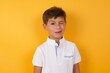Leinwandbild Motiv Cute Caucasian little boy standing against yellow background  blinking eyes with pleasure having happy expression. Facial expressions and people emotions concept.