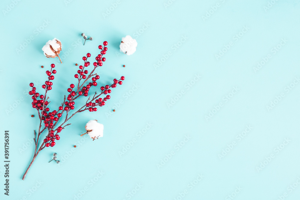 Fototapeta Christmas composition. Red berries, cotton flowers on blue background. Christmas, winter, new year concept. Flat lay, top view