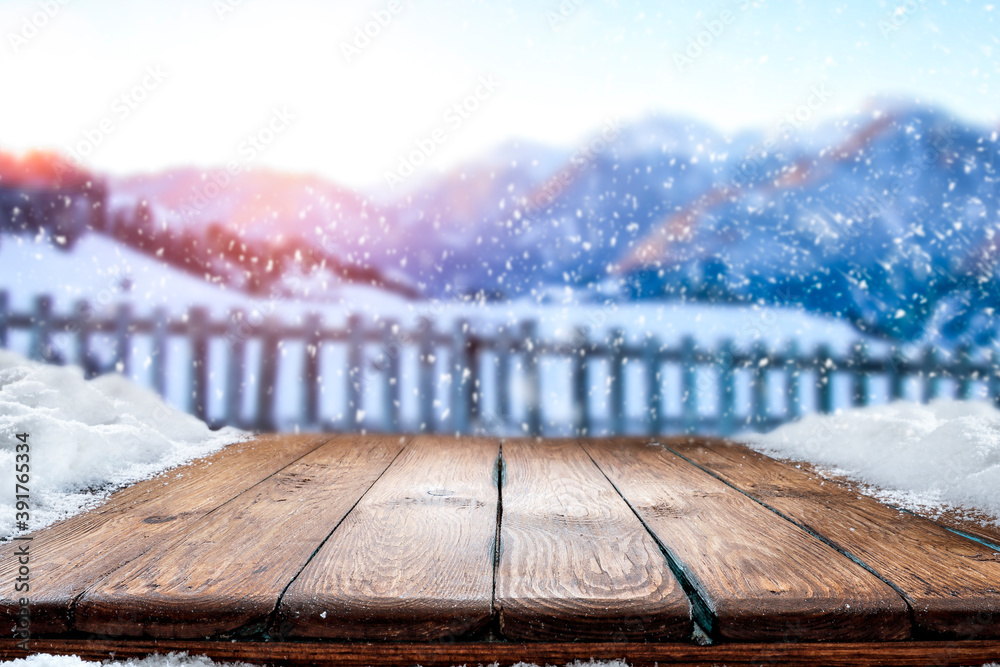 Fototapeta Wooden table in the snow against the backdrop of a mountain landscape at sunset