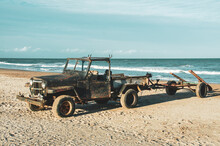 Old And Rusty Black Color Vehicle Without A Roof On The Sand On The Shore Of The Blue Sea With Motorboat Cart And The Blue Sky With Clouds In The Background