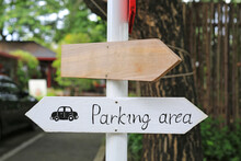 Direction Parking Area Sign On Wooden Panel With Arrow On The Pole.