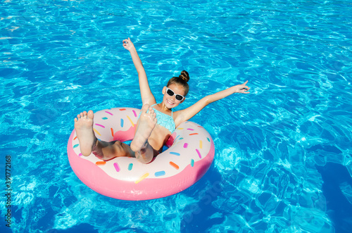 Fotografiet Cute smiling little girl in swimming pool with rubber ring