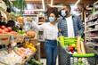 Leinwandbild Motiv African American Couple Doing Grocery Shopping Together Buying Food