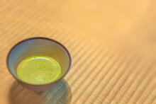 Background Of A Ceramic Ware Chawan Cup Of Japanese Matcha Green Tea On A Tatami Mat Covered With Woven Soft Rush Straw In A Traditional Japanese-style Room.