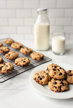 Freshly Baked Chocolate Chip Cookies And Milk On White Marble Counter.