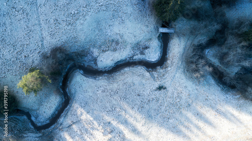 Canvas Print Aerial view of meandering river on snow covered ground