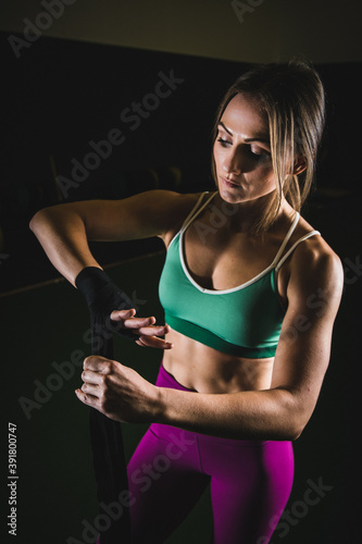 Beautiful female boxing and fitness athlete training in gym.