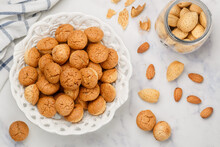 Amaretti-traditional Italian Almond Cookies In A White Plate On A Marble Top View Background. Amarettini Biscuits. Selective Focus