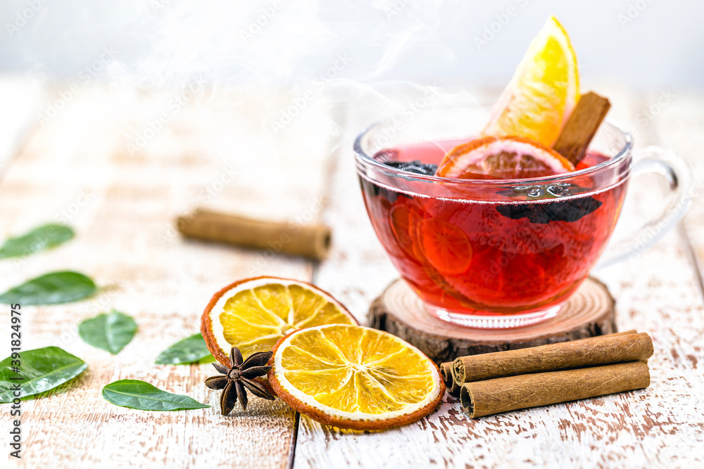 Fototapeta hot winter drink, with smoke and steam, hot Christmas wine, drink with cinnamon, wine and citrus fruits. Known as mulled wine, Spanish sangria, glogg and Glühwein.
