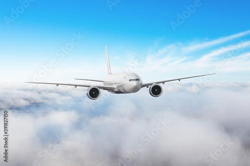 Slika na platnu Passenger airliner flies along the edge of low stratus clouds.