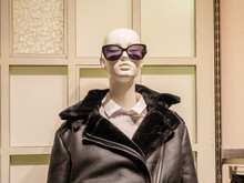 Female Bald Mannequin Wearing Sunglasses And Leather Jacket With Fur Collar