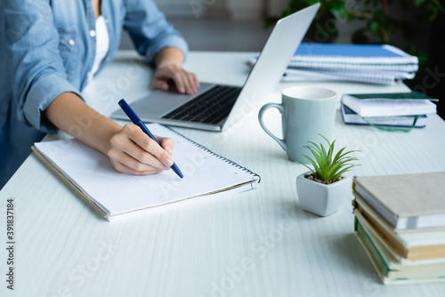 cropped view of woman making notes in notebook and typing on laptop Fototapet
