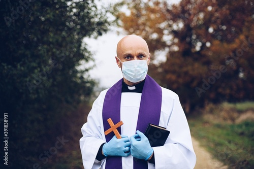 Fotografia, Obraz Man priest in a protective mask and protective gloves during a pastoral visit