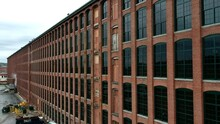 Brick Building Exterior Of Riverwalk Lawrence From Merrimack Street In Lawrence, Massachusetts, USA. - Aerial