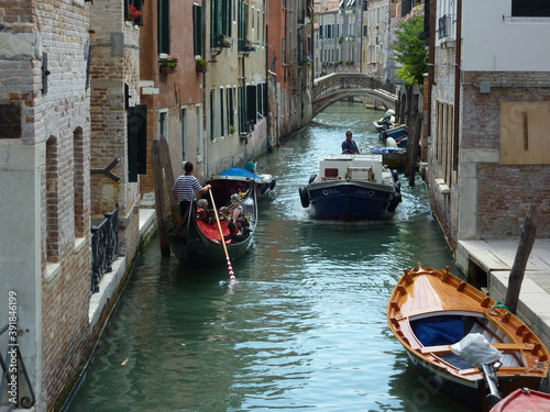 Fotografiet A gondola gives way to a motorboat in a narrow Venetian canal