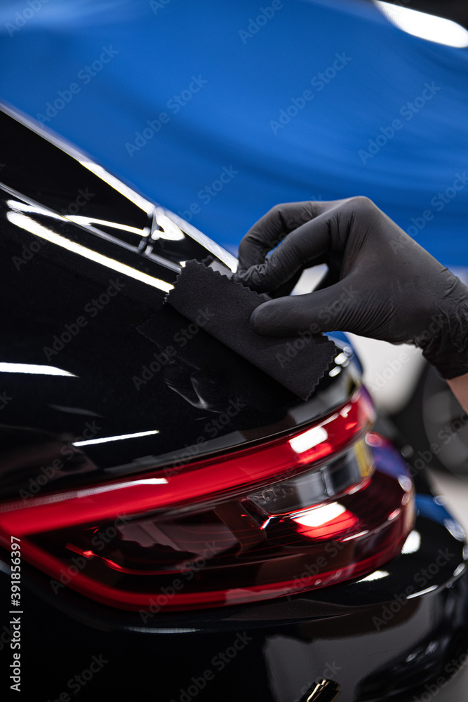 Fototapeta Car detailing studio worker applying car ceramic coating