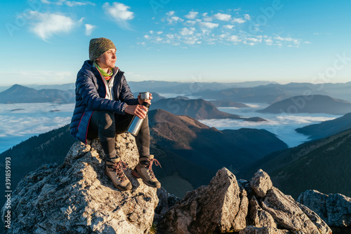 Obraz Young hiker woman sitting on the mountain summit cliff, drinking tea from a thermos flask and enjoying mountains valley covered with clouds view. Successful summit climbing concept image. - fototapety do salonu