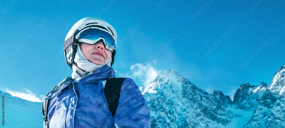 Fototapeta Skier female portrait in safe ski helmet and goggles with picturesque snowy Tatry mountains background.