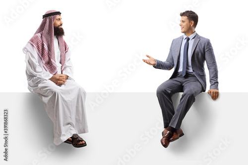 Papel de parede Saudi arab man and a young man in a suit sitting on a blank board and talking