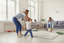 Happy Mom And Dad With Little Son Spending Time At Home And Playing With Inflatable Ball