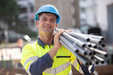 Worker Carrying Pipes On His Shoulder On Construction Site