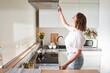 Leinwandbild Motiv Woman select mode on cooking hood