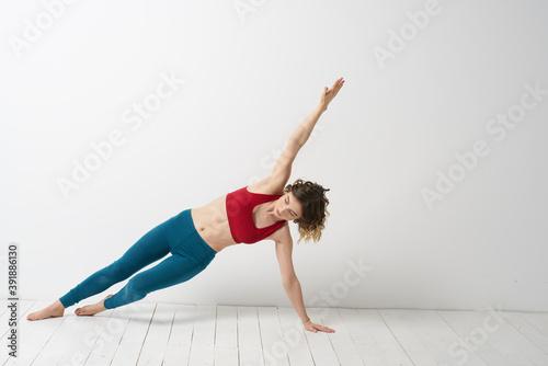 Obraz woman in leggings is engaged in gymnastics in a light room slim figure fitness sport - fototapety do salonu