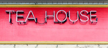 Neon TEA HOUSE Sign Mounted On Red Wall With Yellow Border.