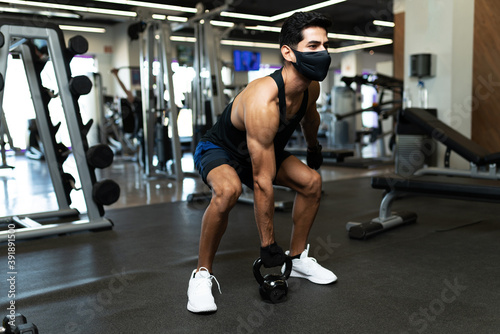 Fototapeta Hispanic young man training with a dumbbell obraz