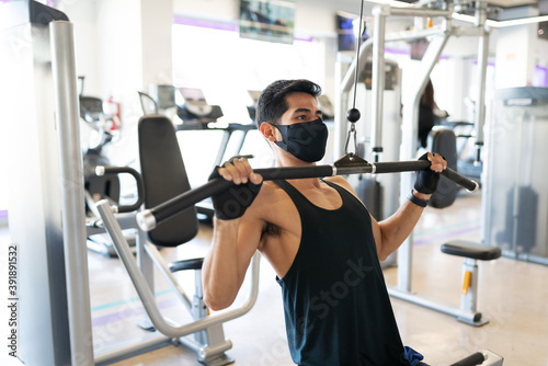 Tela Young man with a mask exercising in the cable machine