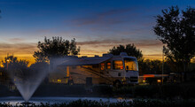 Camping At A Rv Park With A Water Fountain With Lights Under A Colorful Sunset Sky With Rv Interior Lights On