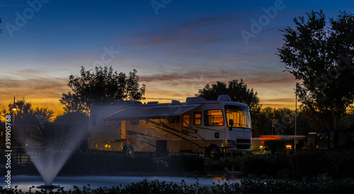 Tablou Canvas Camping at a Rv park with a water fountain with lights under a colorful sunset s