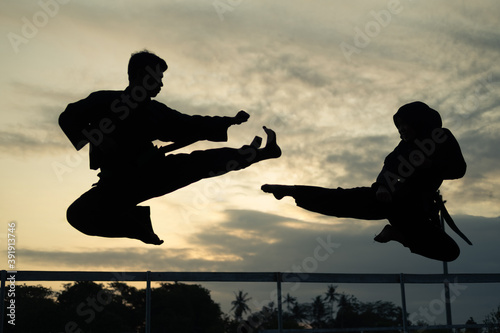 silhouettes of two fighters with kicks drifting in the sunset background Fotobehang