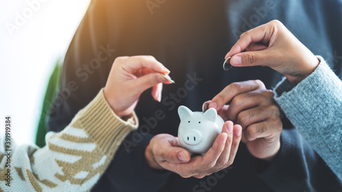 Fotografía Closeup image of people holding and putting coin into piggy bank for saving mone