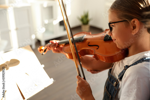 Obraz na plátně Cute little girl playing violin indoors, closeup. Music lesson