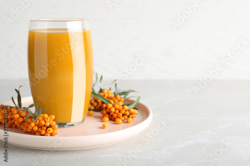 Delicious sea buckthorn juice and fresh berries on light grey marble table. Space for text