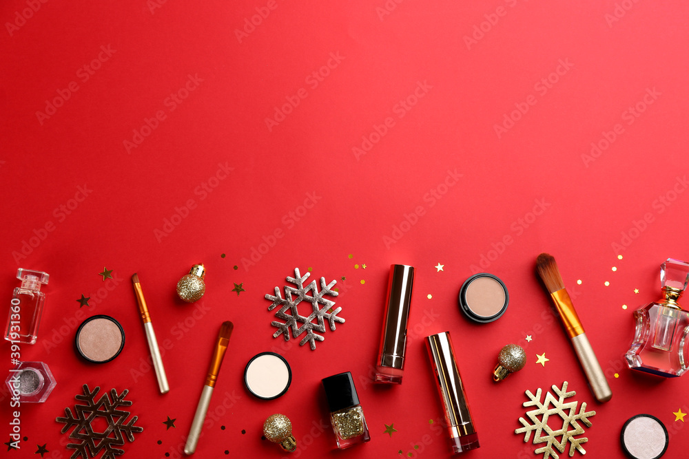 Fototapeta Flat lay composition with decorative cosmetic products on red background, space for text. Winter care
