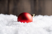 Christmas Balls On The Artificial Snow With Rustic Wooden Background. Selective Focus. Shallow Depth Of Field.