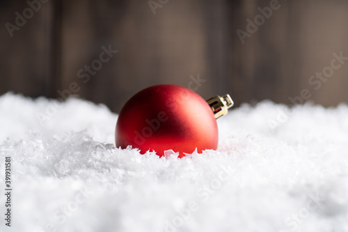 Christmas balls on the artificial snow with rustic wooden background Canvas Print