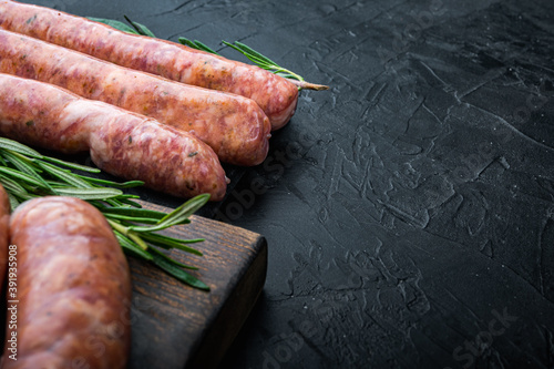 Obraz na płótnie Raw homemade beef sausages with space for text, on black background