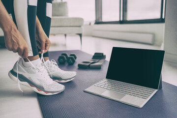 Panel Szklany Tenis Home workout with laptop. Online fitness class . Woman getting ready for exercising tying her running shoes with technology device streaming on black screen.