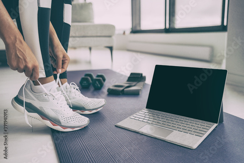 Fototapeta premium Home workout with laptop. Online fitness class . Woman getting ready for exercising tying her running shoes with technology device streaming on black screen.