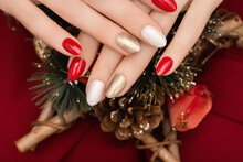 Female Hand With Christmas Nail Design. Red And Gold Nail Polish Manicure. Female Hand Hold New Year Decoration.