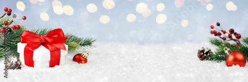 Wide panorama banner design image with festive Christmas decoration ornaments in winter landscape with gift box and decorations